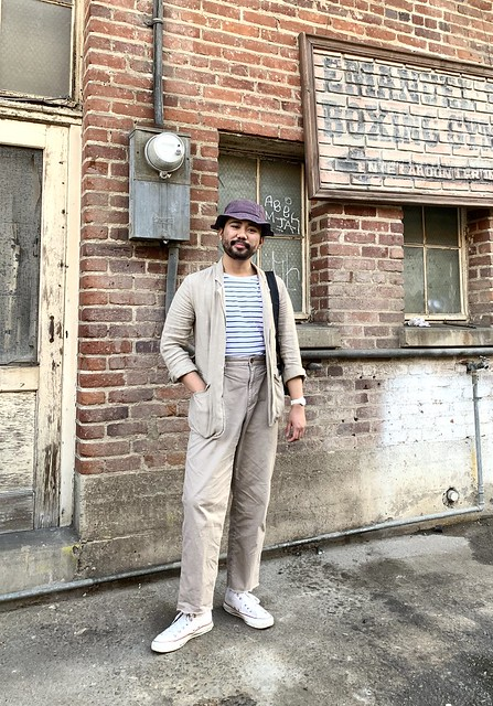 Ethan - casual suit - bucket hat. Linen chore blazer, raw hem cut off pleated chinos, white socks, striped white shirt, converse
