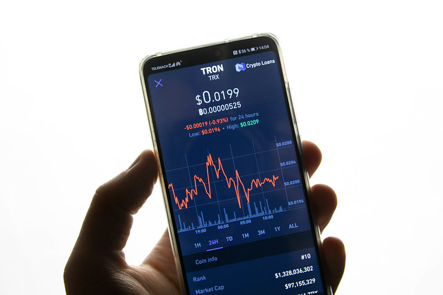 A smartphone displays the Tron market value on the stock exchange | by wuestenigel