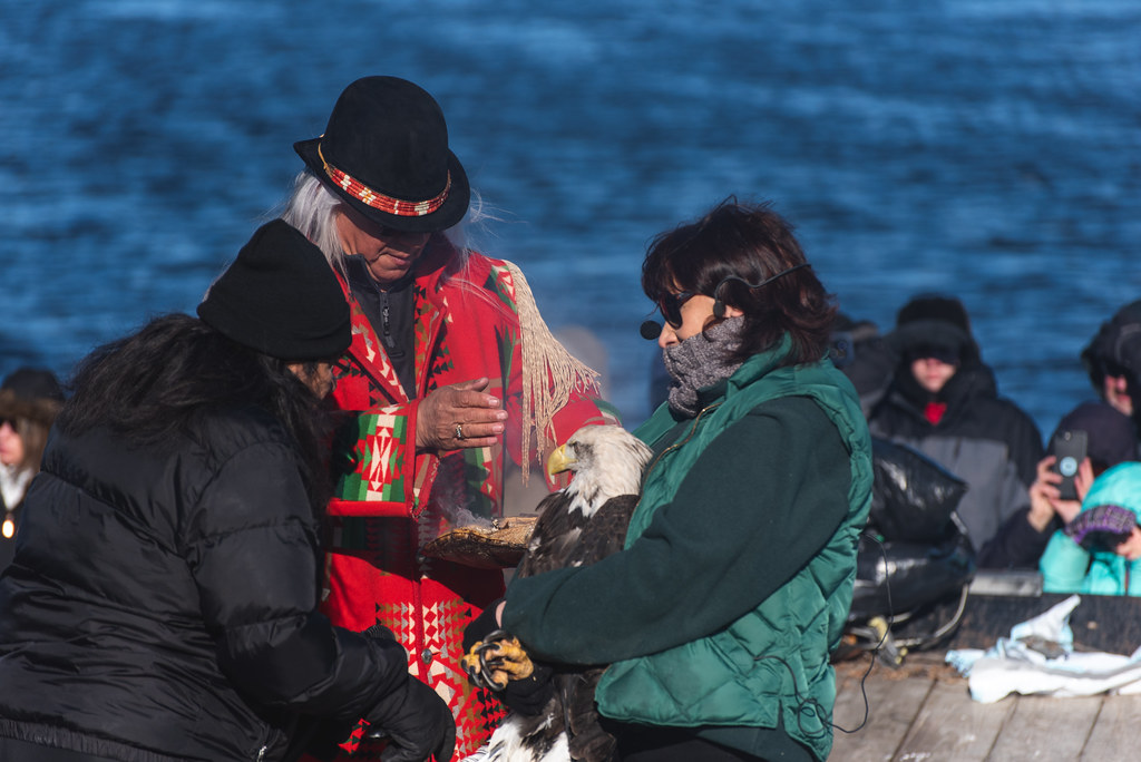 Two tribe members perform a ritual over a bald eagle held by a woman.