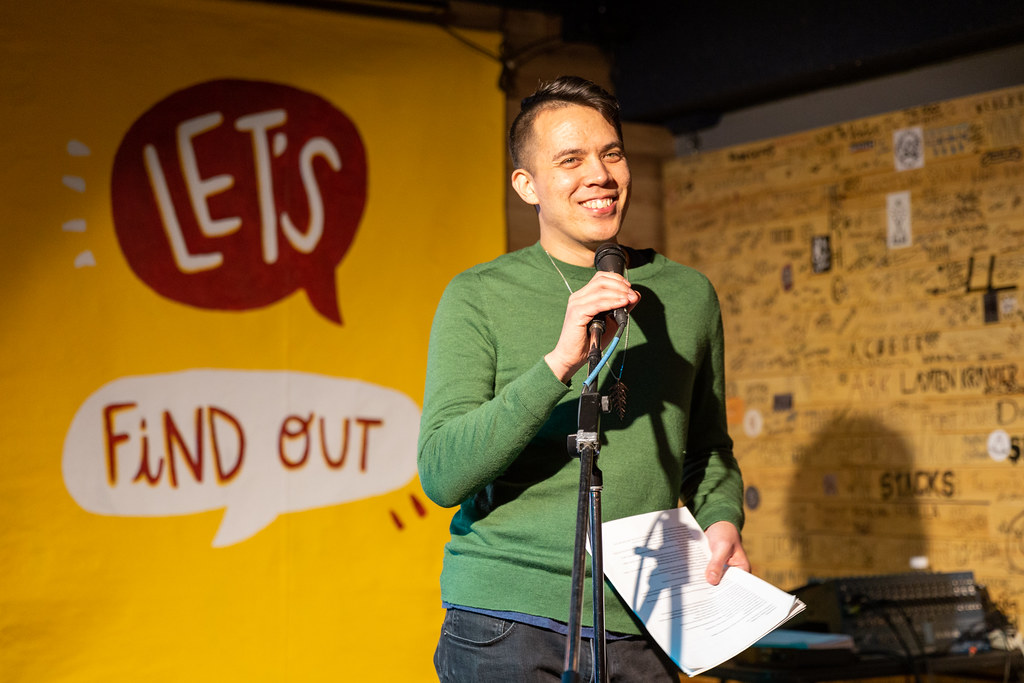 Chris Chang-Yen Phillips smiles at a microphone in front of a popup banner for Let's Find Out