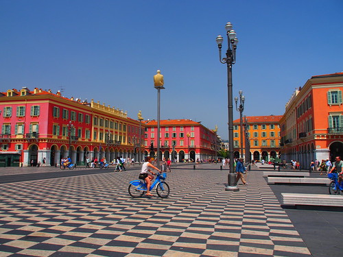 place massena ville france damier nice square city cityscape people architecture beautiful building biker bike vue view street lamp child arch pattern red orange yellow