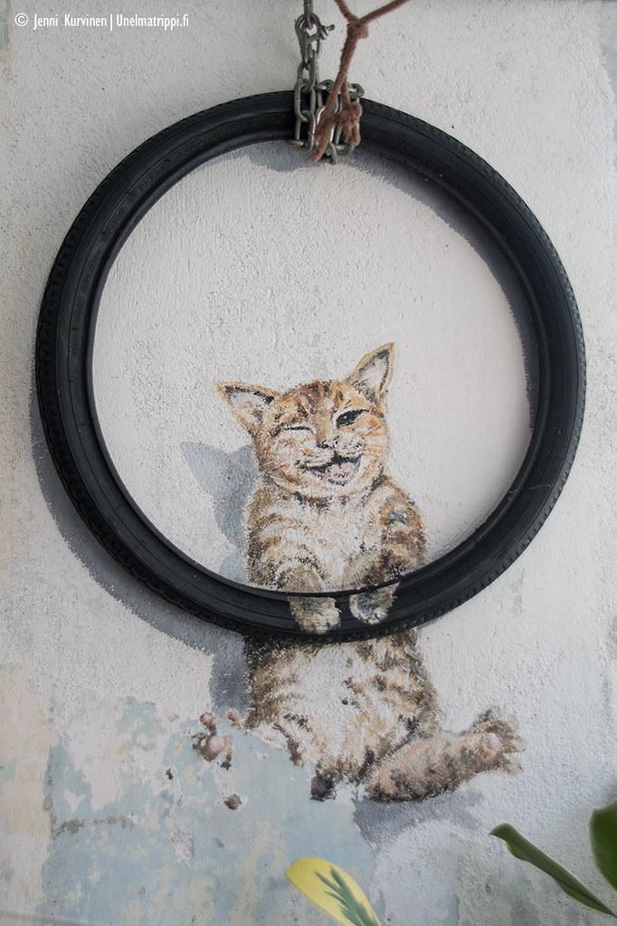Katutaideteos renkaan sisällä olevasta kissasta