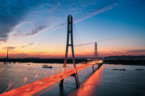 nanjing jiangsu china cn bridge cablestayedbridge drone aerial sunset twilight dusk river transportation boat ship cloud reflection highway skyline sky architecture building blue orange landscape