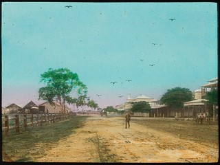Man walking across an unsealed road in the main street of a town, Queensland, ca. 1910