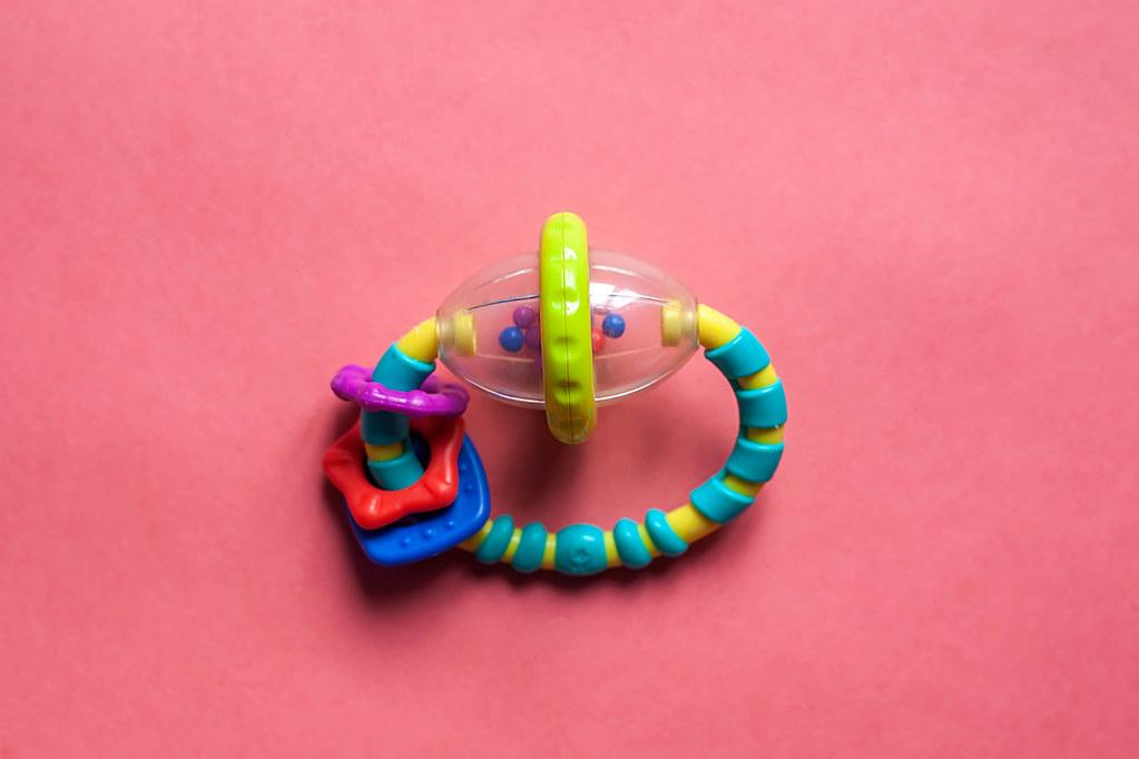 plastic newborn babies rattle on a pink background  flat l