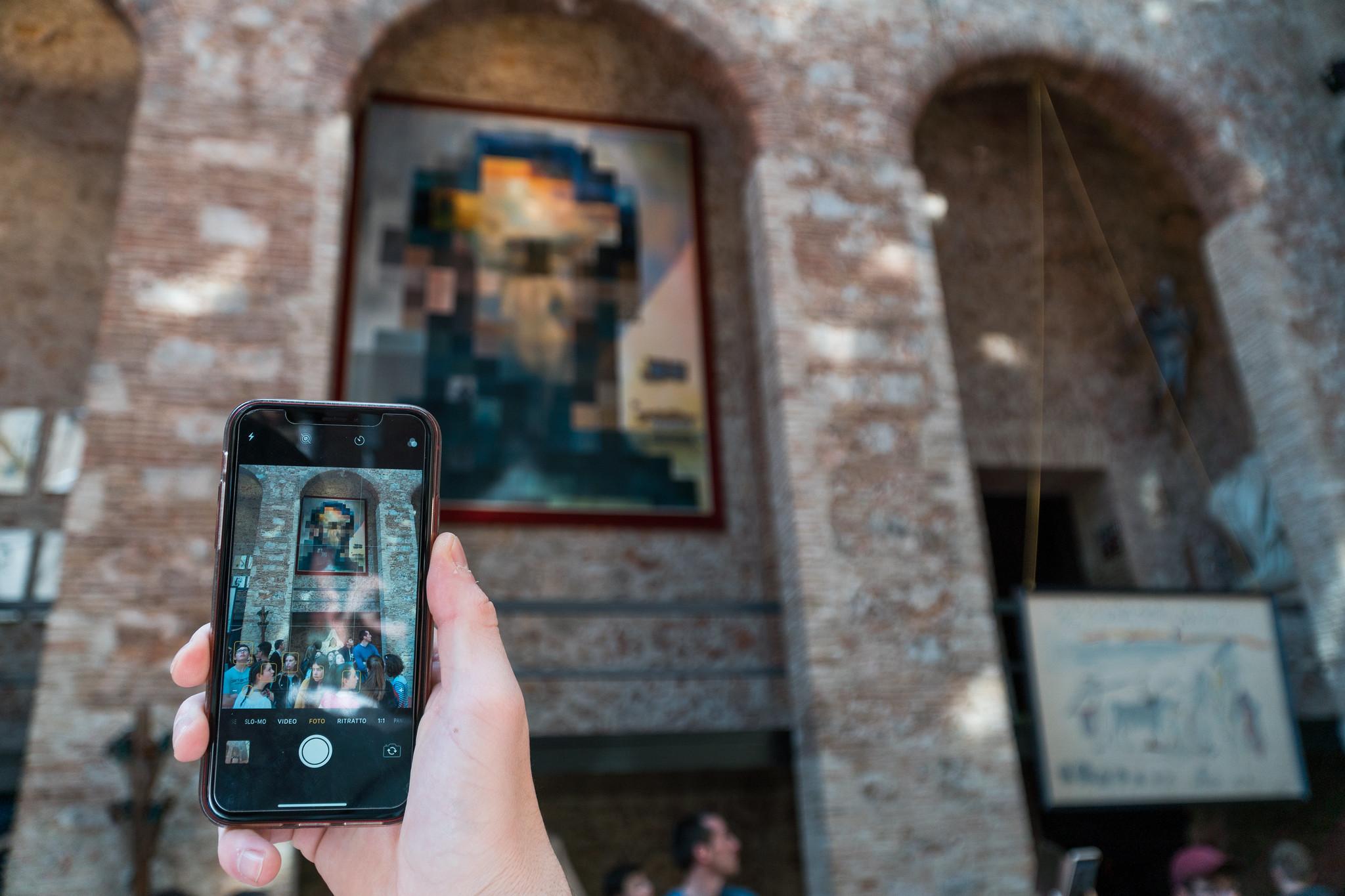 un telefono inquadra un dipinto di un apparente volto