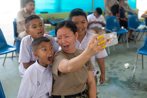 Sailor poses for a selfie with children during a community outreach event. | by Official U.S. Navy Imagery