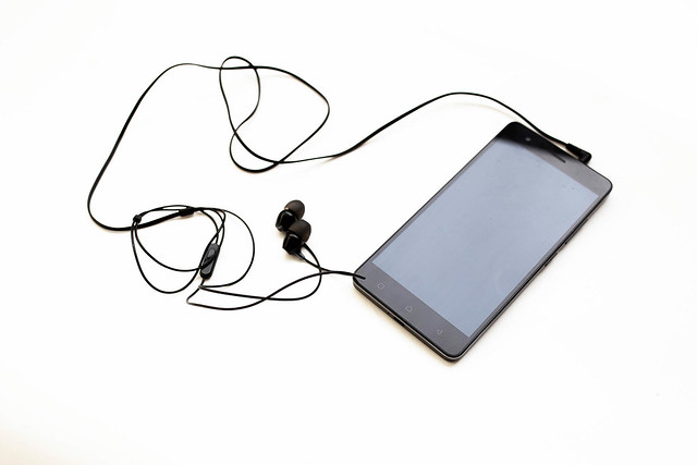 Black smartphone with earphones on white background