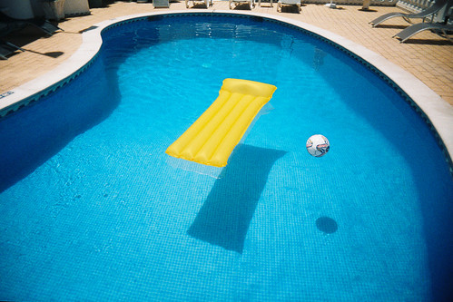 yellow floatie and a volleyball floating in a backyard pool