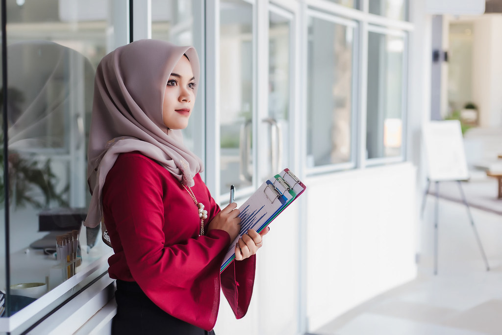 Young asian muslim woman teacher holding documents and learning plan.