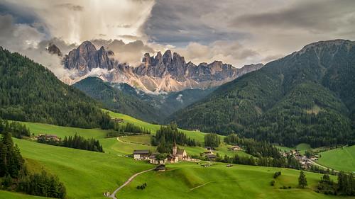 alpine church cloud dolomites dolomiti geisler grass green jagged meadow mountain odle peak santamaddalena villaged