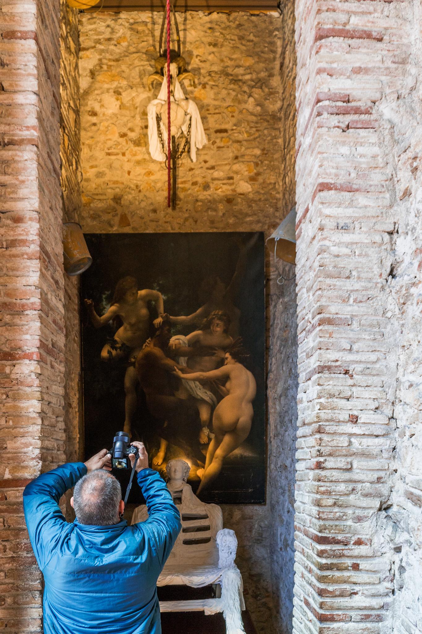 un uomo scatta la foto di un dipinto più in alto di lui