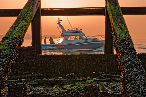 dawn sunrise anglers boat daybreak tide barrier wood seaweed sea ocean water glow amber ghe