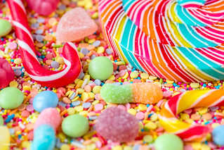 Close up of candycane and lollipop on a colorful sweets background | by Rawpixel Ltd