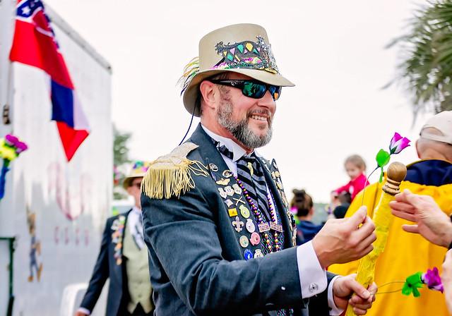 Ole Biloxi Marching Club giving flowers at Krewe de la Dauphin Mardi Gras parade in Dauphin Island, Alabama