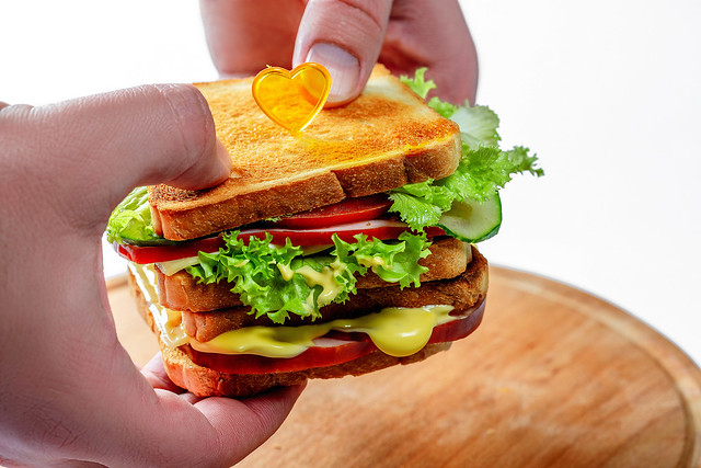 Man holding sandwiches with ham, cheese, vegetables and cheese sauce