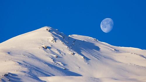 outdoors reschen südtirol altoadige astronomy sunny winter white blue sky snowcapped snow moon alps peak mountain mountains alpine landscape