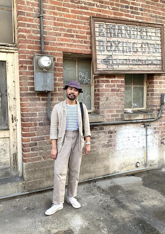 Ethan - casual suit - bucket hat. Linen chore blazer, raw hem cut off pleated chinos, white socks, striped white shirt, converse