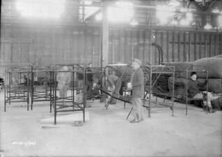 Repairing and painting bedsteads in hangar A-3, Relief Project No. 28 during the Depression, Trenton, Ontario / Réparation et peinture de lits dans le hangar A-3, programme d'assistance-chômage no 28, pendant la Dépression, Trenton (Ontario)