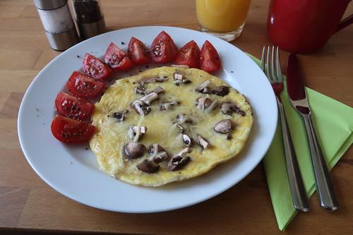Omelett mit Käse sowie Champignons und dazu Tomatenspalten