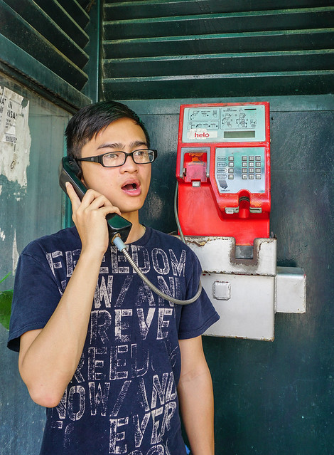 Young Asian man talking on street phone
