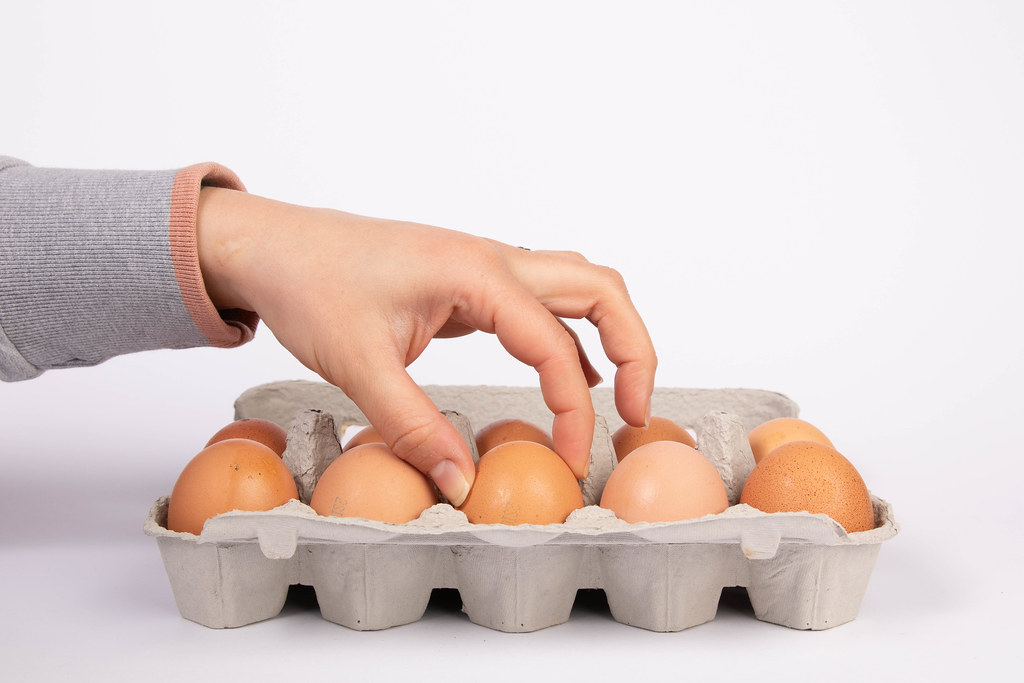 Woman hand selected egg in egg carton on white background | Flickr