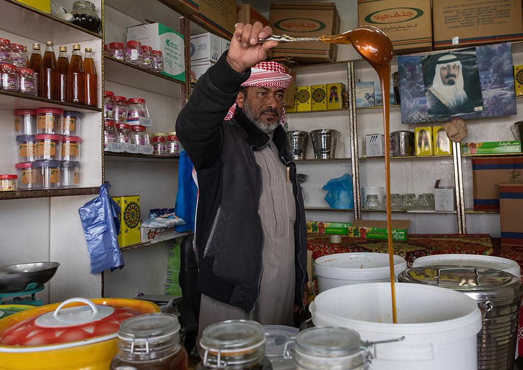 Saudi man selling honey in a shop, Asir province, Abha, Sa