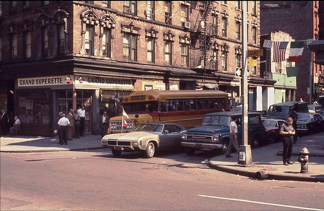 Several older guys in white shirts mill around around the Grand Superette while a cool 1969 Buick Riviera waits for the light at the corner of Grand and Mott Streets. Little Italy. New York. June 1970