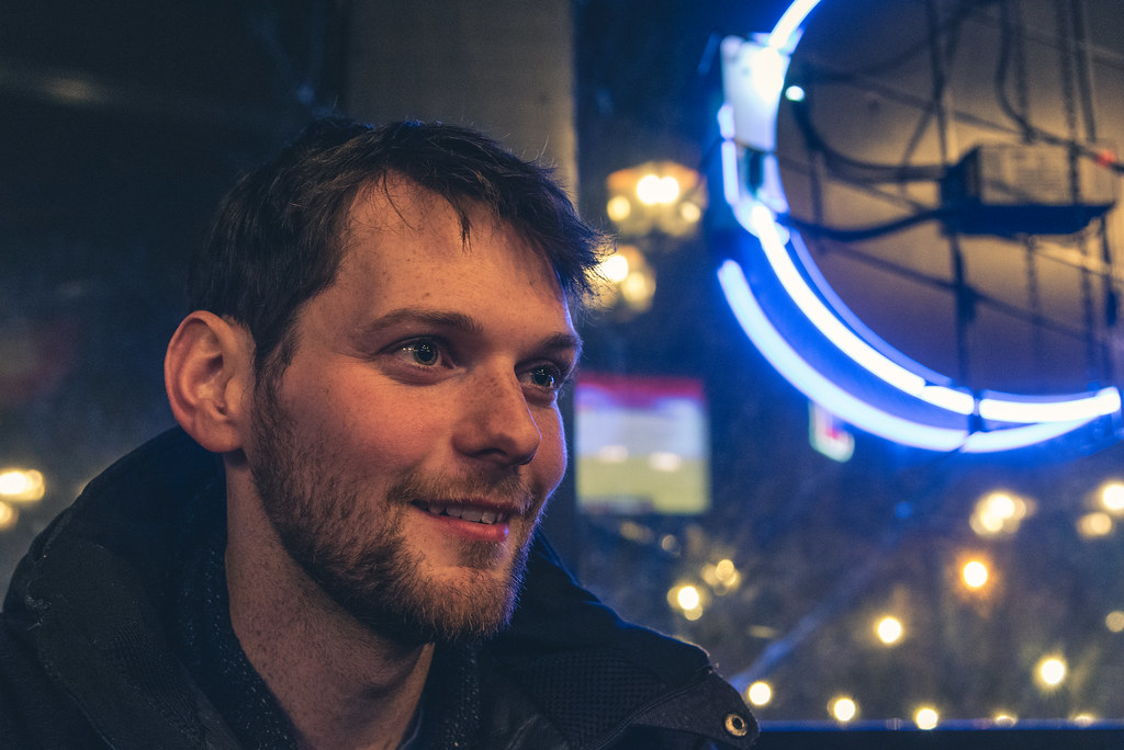 A portrait taken at a bar with neon in the window behind.