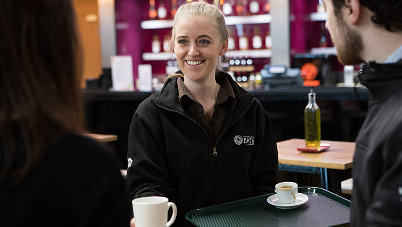 Food and beverage assistant serving coffee
