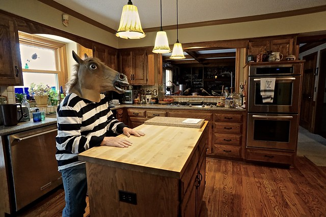 Strange Man in the Kitchen Wearing a Striped Shirt and a Horse Mask
