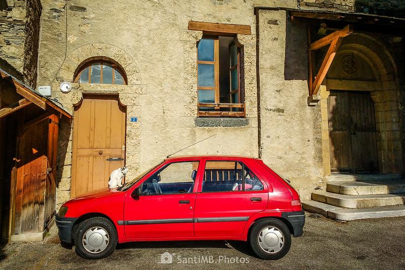 Gato sobre un coche frente a la rectoría de Saint-Martin d'Unac