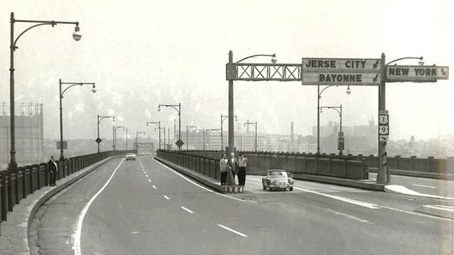 I've been trying to figure this one out for a while. Two formally dressed men and a woman stand precariously at a Pulaski Skyway entrance. The woman is pointing at something. Across the highway stands a third man, also in a suit. Jersey City. 1967