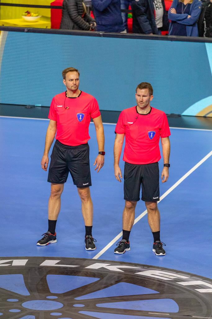Zwei Schiedsrichter der Handball WM 2019 stehen nebeneinander auf Spielfeld