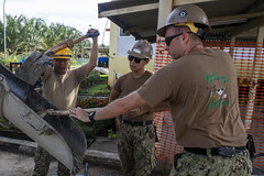 A Malaysian Army soldier and U.S. Navy Seabees pour concrete during a project at a school in Kuching, Malaysia. (U.S. Navy/MC1 Nathan Carpenter)