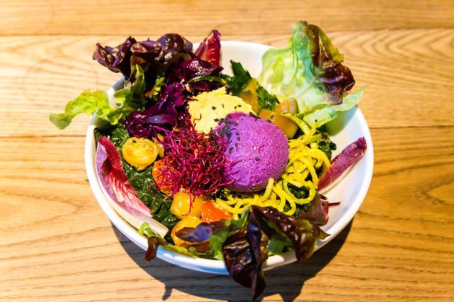 Salatmix, Orangen- und Rotkohl-Hummus, Zucchini-Tagliatelle mit Kurkuma-Pesto, Tomaten, Basilikum im Flax&Kale in Barcelona