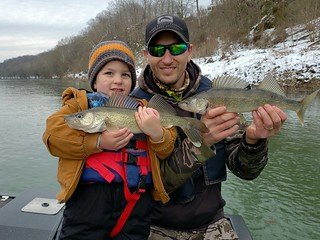 Photo of man and boy holding up two walleye