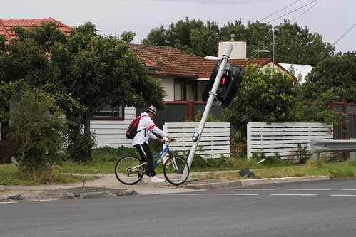 Cyclist waiting beside a smashed traffic light post