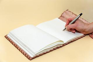 Woman hand  writes in the notepad   by wuestenigel
