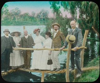Group of men and women standing on a small wooden structure on the banks of a river, Queensland, 1910