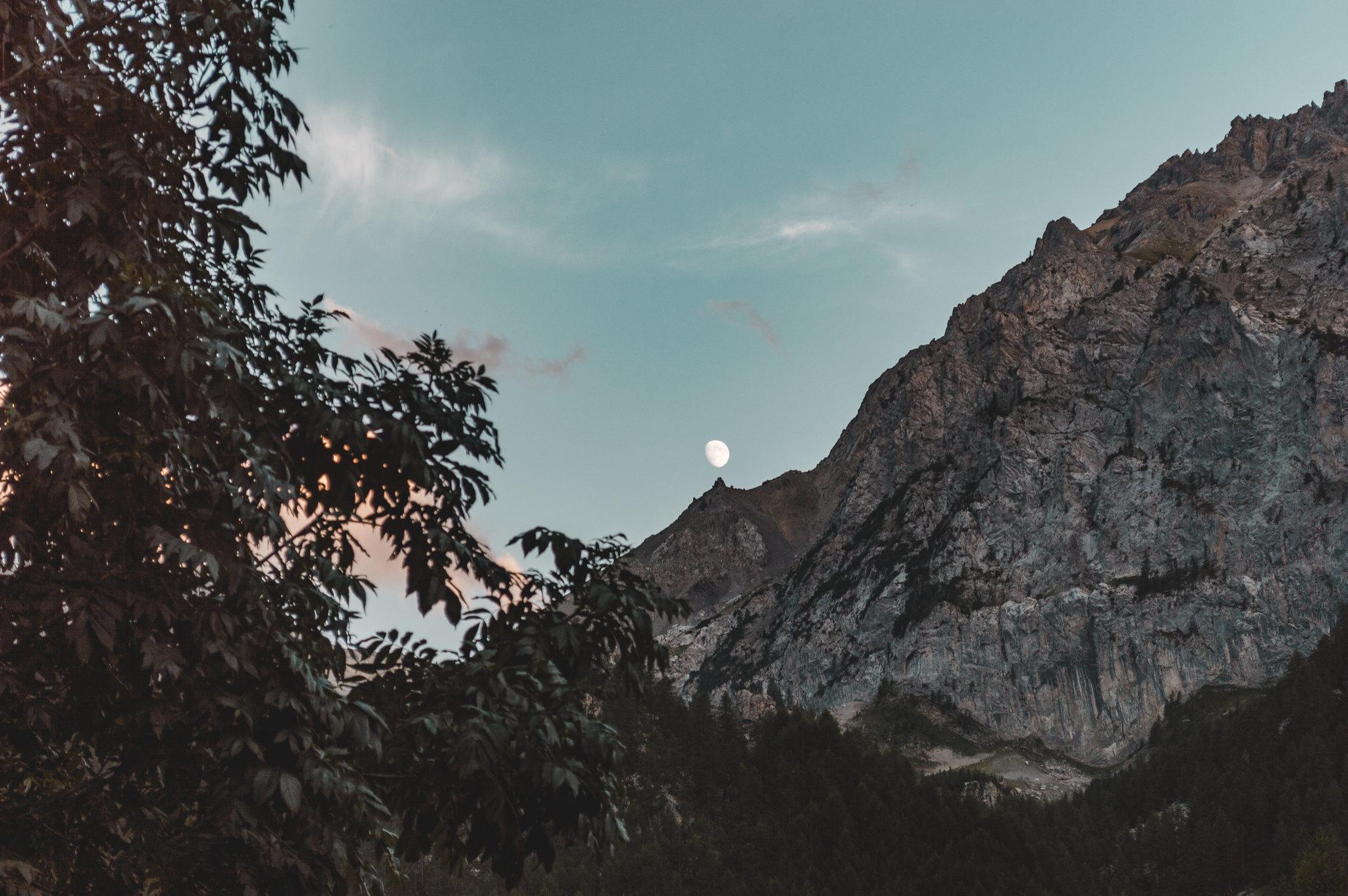 la luna sospesa sul picco di una montagna
