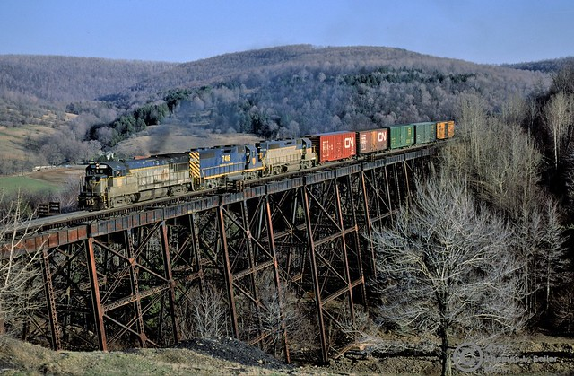DELAWARE & HUDSON TRAIN #NE-84 ROLLS NORTH OVER THE TRESTLE AT STARRUCCA - STARRUCCA, PENNSYLVANIA - APRIL 19, 1980