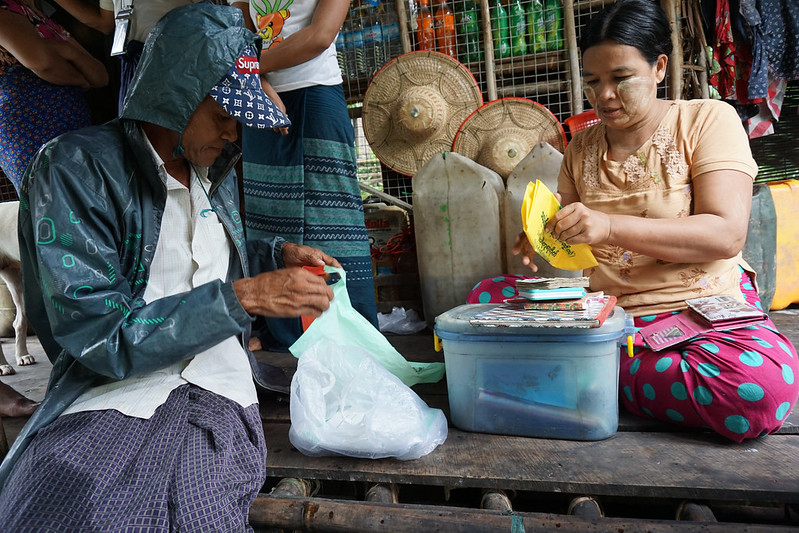 Daw Cho Mar in her store buying fish from fisherman.