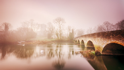 uk england bedfordshire felmersham river ouse morning mist misty fog foggy swan swans church bridge