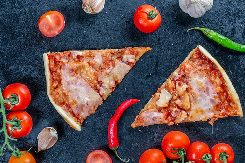 Two slices of homemade pizza on a black background with vegetables. Top view | by wuestenigel
