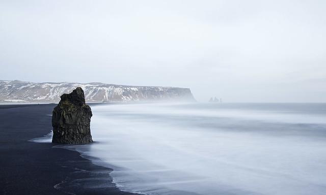 La marée en blanc écrit sur une plage noire
