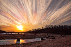 Frozen Hay Bales Under a Sky of Fire