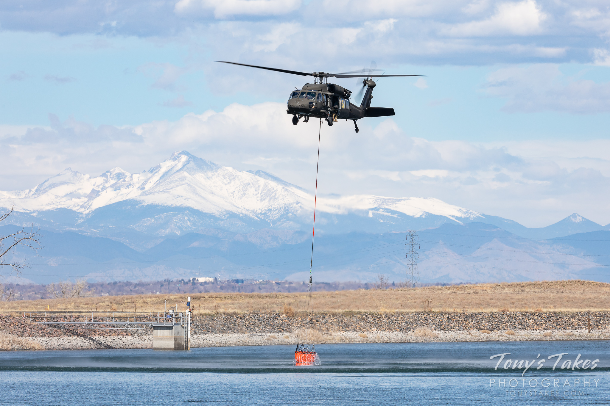 A Colorado National Guard UH-60 Blackhawk picks up water in a firefighting bucket with the snow-capped mountains in the background. (© Tony's Takes)