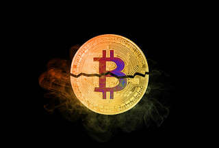 Bitcoin broken in half with colorful smoke on black background | by wuestenigel