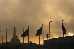 Mosque, mist, flags and sun